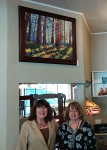 24x30 inch oil painting Redwood Mist, hanging above shop owner Sharon and artist Michele..